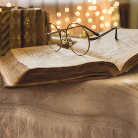 聖書本の眼鏡。背景にクリスマス ライト。