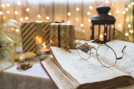眼鏡と聖書の本。背景にクリスマスライト。
