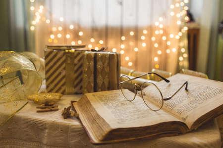 Libro della bibbia santa con gli occhiali. Luci di Natale sullo sfondo. Archivio Fotografico
