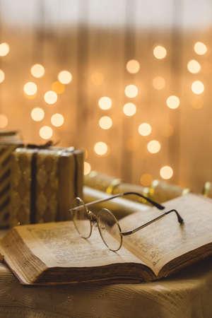 Livre de la Sainte Bible avec des lunettes. Lumières de Noël sur fond.