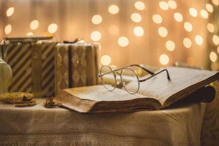 Heilig bijbelboek met oogglazen. Kerstverlichting op achtergrond. Stockfoto