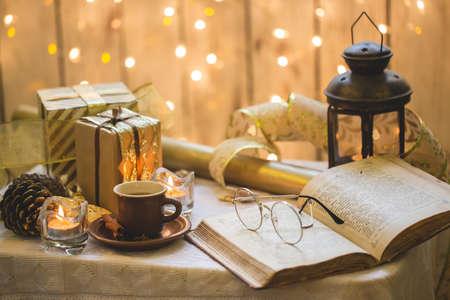 眼鏡をかけた古い本。背景にクリスマスの飾り。杯のコーヒー