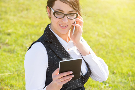 Young business woman with tablet and phone