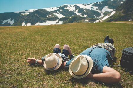 Adventures in the Rila Mountains of Bulgaria. Family on vacation. Dad and son dressed as hipsters laying on the green grass. Route seven Rila lakes Banco de Imagens