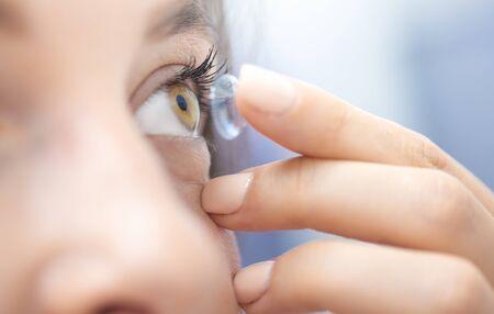 Nahes Porträt einer schönen Frau, die Kontaktlinsen aufsetzt. Die Kontaktlinse liegt auf der Fingerspitze. Konzept zur Sehkorrektur