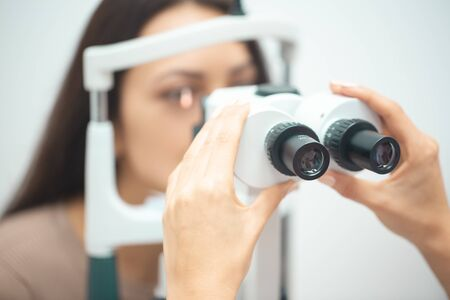 Diagnostic cabinet A young girl is diagnosed with vision and contact lenses are selected.