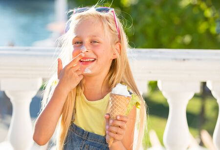 Little girl enjoy ice cream in a vaiel glass. Teen is fashionably dressed. Child posing against the backdrop of street scenery Imagens