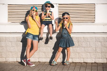 Two sisters and their brother enjoy ice cream in a vaiel glass. Teenagers are fashionably dressed. Children posing against the backdrop of street scenery