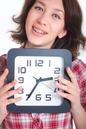 Girl in a plaid shirt with multi-colored braces holding a watch