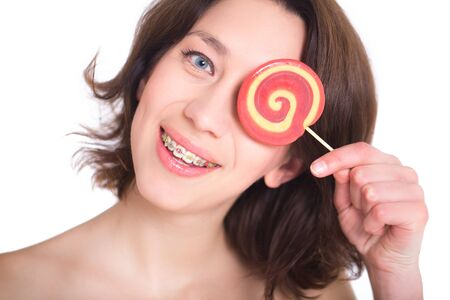 Close-up shot of girl with multicolored bracket systems and lollipop Stockfoto