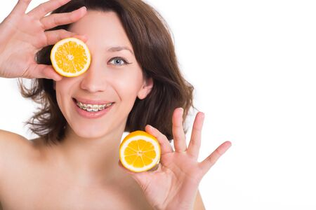 Beautiful girl with perfect skin and multi-colored braces posing with lemon on palm