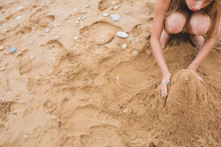 Little girl playing with sand on the beach. Build castles from sand. Lifestyle photo view from above