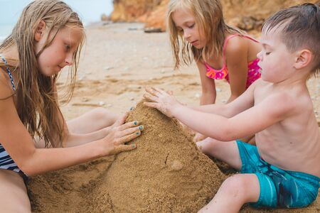 Brother and sisters are playing with sand on the beach. Build castles from sand. Lifestyle photo Stockfoto