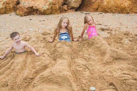 Brother and sisters are playing with sand on the beach. Lifestyle photo