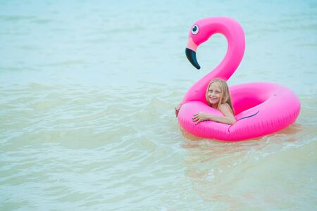 A girl is playing on the beach with an inflatable flamingo. the hit of the season