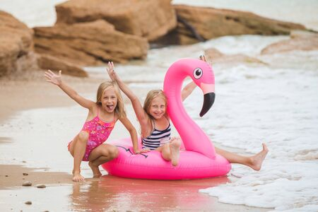 Girls are playing on the beach with an inflatable flamingo. the hit of the season. two sisters