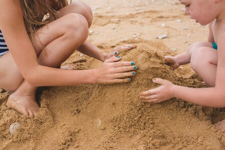 Brother and sister are playing with sand on the beach. Build castles from sand. Lifestyle photo Stockfoto - 144495950