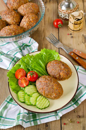 Cutlets with buckwheat and a side dish of vegetables. On the plate are lettuce, cucumbers and tomatoes. photo