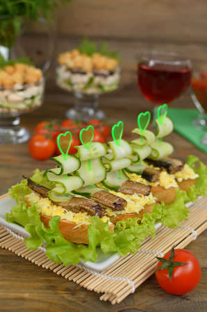 sprat: Sandwiches with sprat, egg and cucumber. Fresh food Stock Photo