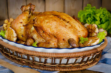 Whole roasted chicken stuffed with buckwheat and mushrooms on wooden table photo