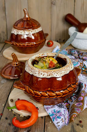 A pot of chicken and mushrooms. Chicken, potatoes and vegetables stewed in a pot photo