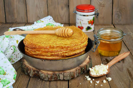 Pancakes with cottage cheese on a wooden table. Golden pancakes, baked from dough made from cottage cheese. Celebrating Shrovetide at Russia photo