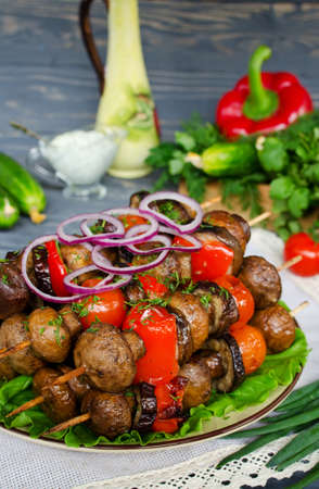 Grilled skewers of mushrooms and vegetables on wooden table photo