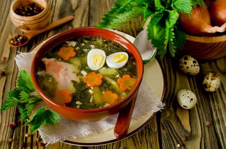 Brandnetel soep met eieren en wortel in de kom op de houten tafel