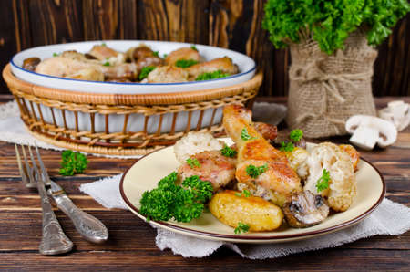 Baked chicken drumsticks with potatoes, mushrooms and cauliflower served on a wooden table. Rustic style photo