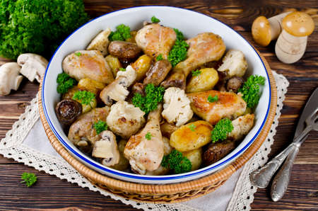 Baked chicken drumsticks with potatoes mushrooms and cauliflower served on a wooden table. Rustic style photo