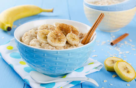 Oatmeal with banana honey and cinnamon. Breakfast on a blue background Standard-Bild