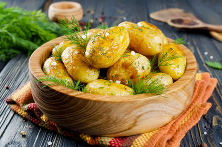 prepared potato: Young roasted potatoes with dill in a wooden bowl Stock Photo