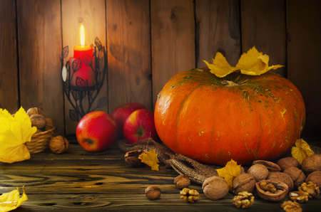 thanksgiving cornucopia: Halloween - pumpkin, nuts, apples by candlelight in autumn colors Stock Photo