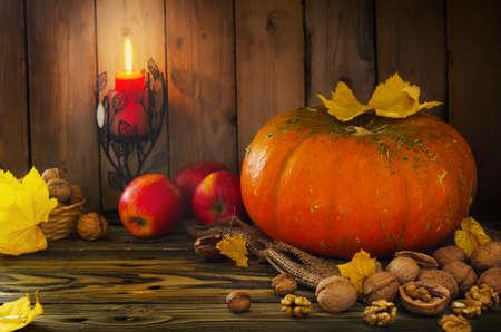 Halloween - pompoen, noten, appels bij kaarslicht in de herfst kleuren Stockfoto