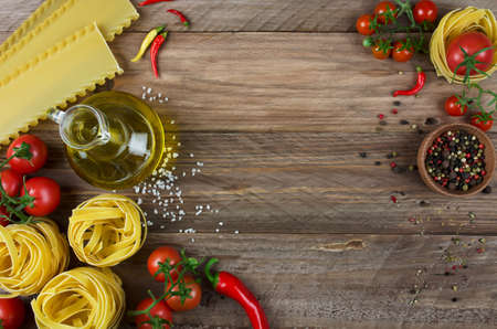 view top: Fettuccine, lasagna, oil and fresh tomatoes on wooden background
