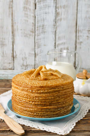 tuesday: A stack of pancakes on a wooden table. Shrove Tuesday