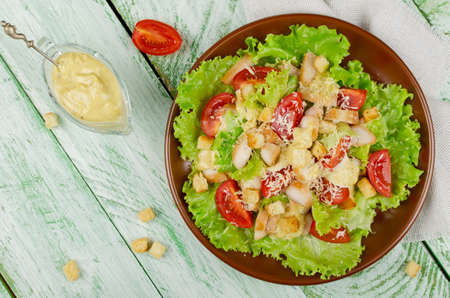 chicken caesar salad: Caesar salad with chicken, croutons and greens on wooden table