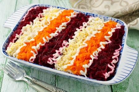 """Traditionele Russische salade """"Haring onder een bontjas"""". Gelaagde salade met haring en groenten Stockfoto"""