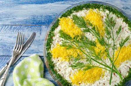 mimose: Insalata con le sarde Mimosas su uno sfondo di legno blu. Insalata decorate con rametti di Mimosa