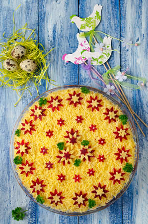 salad decoration: Vegetable salad with spring decoration. Layered salad in a glass dish on a blue wooden background Stock Photo