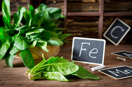 source of iron: Spinach rich in vitamin C, manganese and iron on a dark background