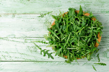 leafy: Fresh green arugula in bowl on wooden table. Arugula is rich in vitamins and trace elements