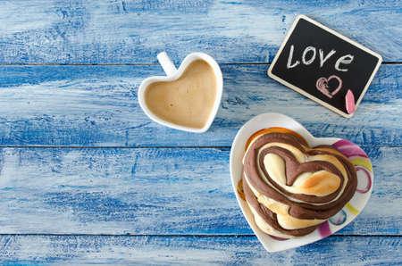 desayuno romantico: bollos dulces de chocolate con café sobre la mesa. desayuno romántico