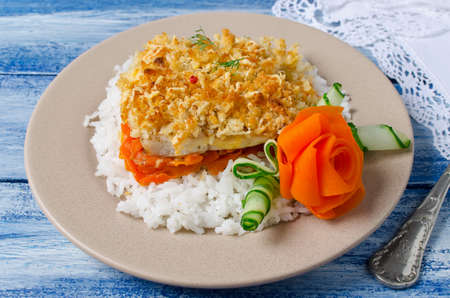 Baked fish fillet with carrots under a bread crust. For garnish white rice Stock Photo