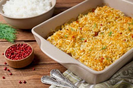 Gebakken visfilet met wortelen onder een broodkorst. Voor de garnering witte rijst
