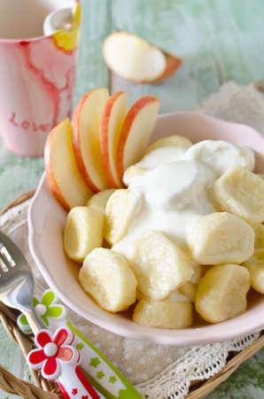 perezoso: albóndigas de descanso de queso cottage con crema agria y manzanas. El desayuno para los niños