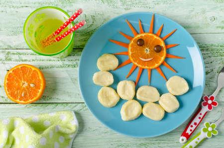 casa de campo: Los niños el desayuno albóndigas perezosos y naranja en la forma de la cara divertida sol. albóndigas de descanso de requesón en la placa azul Foto de archivo