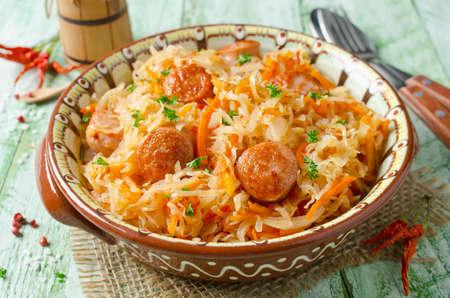 Cabbage stew with grilled sausage - traditional dish of german cuisine