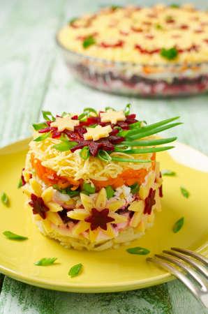 russian salad: Ensalada vegetal con la primavera de decoración. ensalada en capas en un plato de vidrio sobre un fondo de madera azul