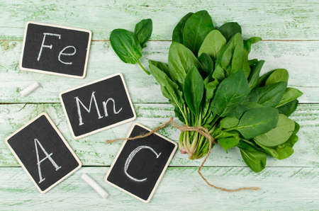 source of iron: Fresh bunch of spinach on a wooden background. Spinach is rich in vitamin C, A, manganese and iron